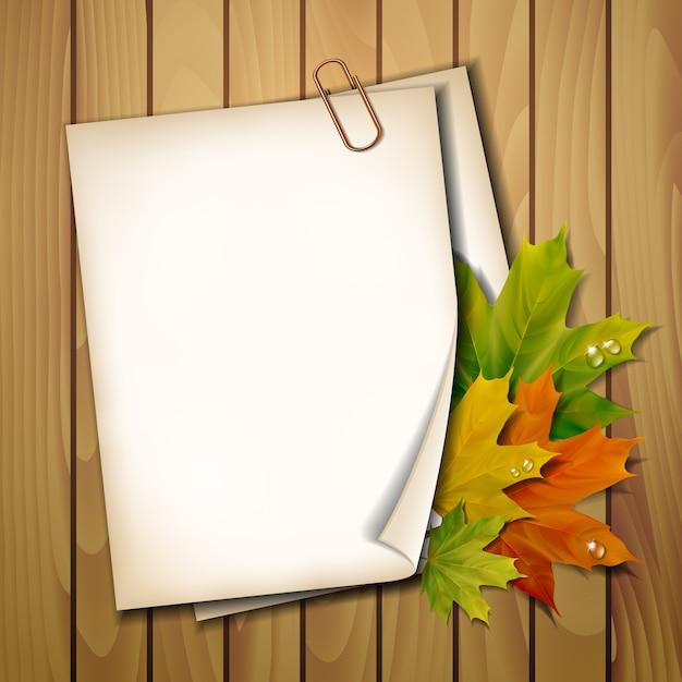 Folha de papel com folhas de outono na textura de fundo de madeira. Vetor Premium