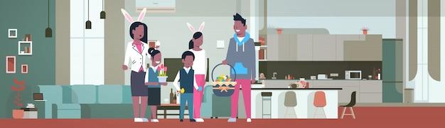 Frican família americana comemorar feliz páscoa férias desgaste orelhas de coelho na sala de estar em casa Vetor Premium