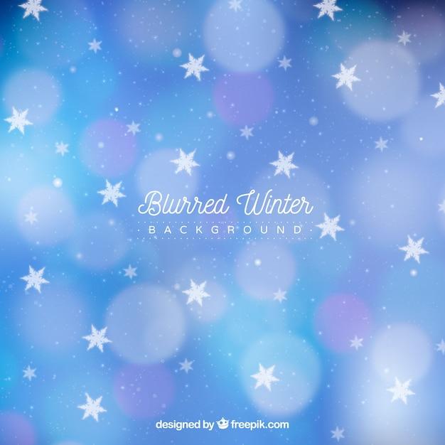 Fundo de inverno borrado com estrelas e flocos de neve Vetor grátis