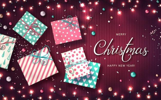 Fundo de natal com luzes de natal, enfeites, caixas de presente e confetes. guirlandas brilhantes de férias de lâmpadas led na textura de malha. decorações de lâmpadas coloridas realistas para cartões de ano novo Vetor Premium