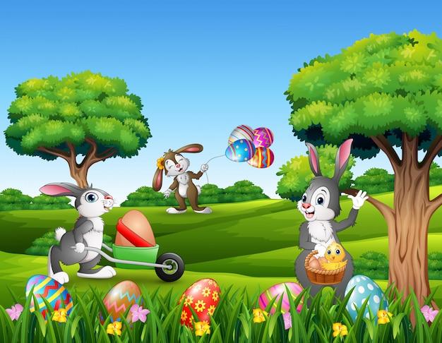 Fundo de páscoa com desenhos animados coelhos brincando na natureza Vetor Premium