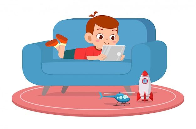 Garoto bonito garoto feliz usar tablet no sofá Vetor Premium