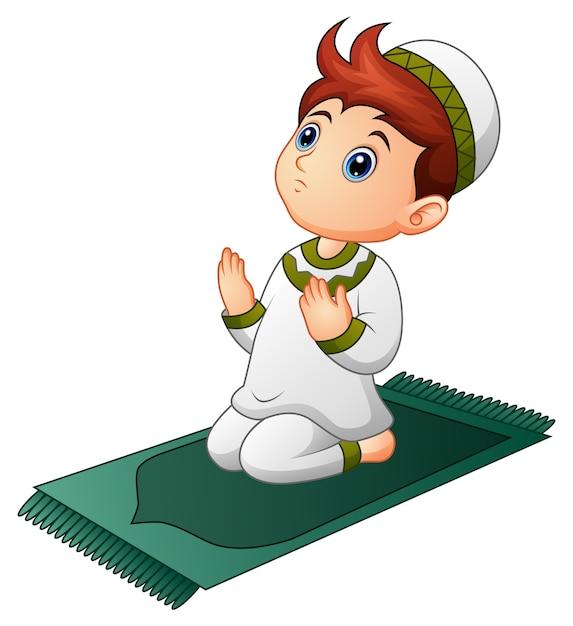 Garoto muçulmano sentado no tapete de oração enquanto orava Vetor Premium
