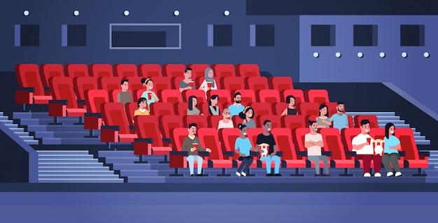 Grupo de pessoas assistindo filme sentado no cinema com pipoca e coca-cola misturam corrida homens mulheres se divertindo rindo de nova comédia apartamento comprimento total horizontal Vetor Premium