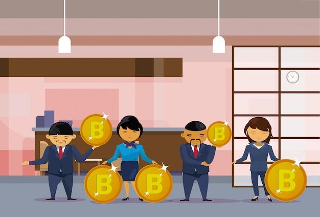 Grupo de pessoas de negócios asiáticos segurando moedas de bitcoins Vetor Premium