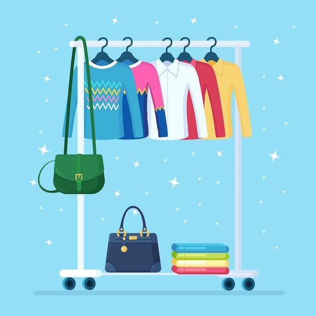 Guarda-roupa para mulher. rack de metal com roupas, bolsas em cabides em boutique. estande de loja com roupas da moda. interior do camarim. Vetor Premium