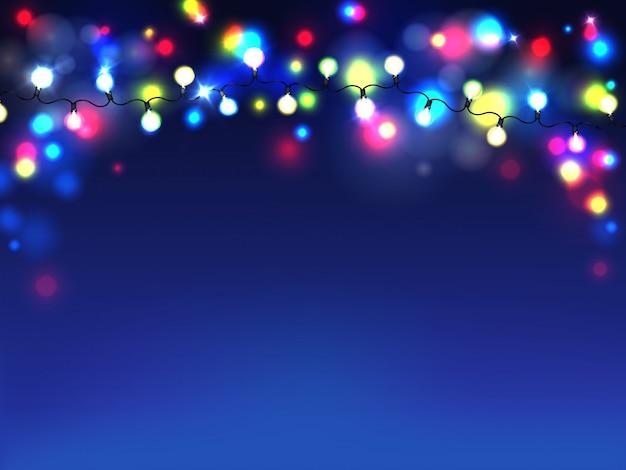 Guirlandas brilhantes isoladas no fundo azul. luzes difusas de lâmpadas elétricas Vetor grátis