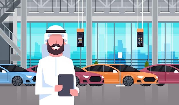 Homem árabe do vendedor no interior da sala de exposições do centro do negociante de carros sobre o grupo de veículos modernos novos Vetor Premium