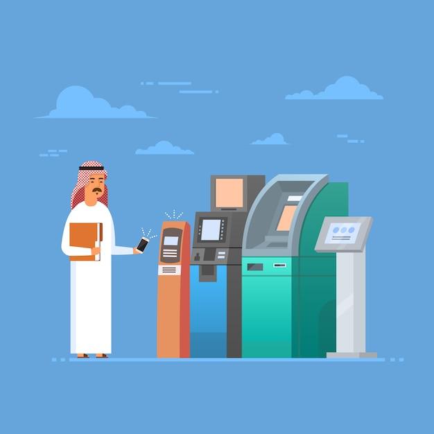 Homem árabe que usa o pagamento móvel do telefone esperto da pilha da máquina do atm, homem de negócios do islão que veste o cl tradicional Vetor Premium