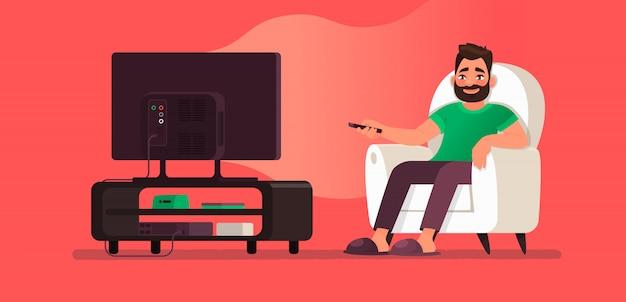 Homem assiste tv enquanto está sentado em uma cadeira. veja o seu programa de televisão ou filme favorito Vetor Premium