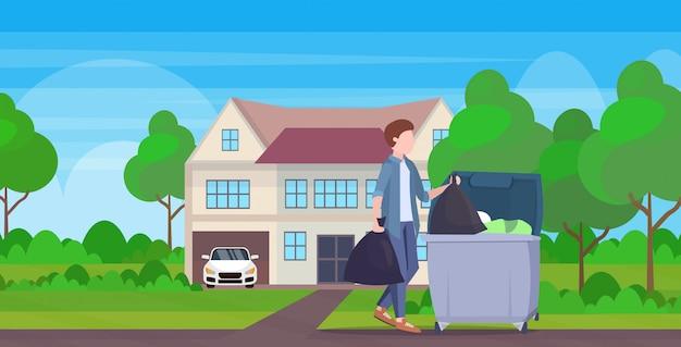 Homem colocar dois sacos de lixo no escaninho de lixo guy novo serviço housework limpeza conceito moderno vila exterior comprimento total paisagem plana fundo horizontal Vetor Premium