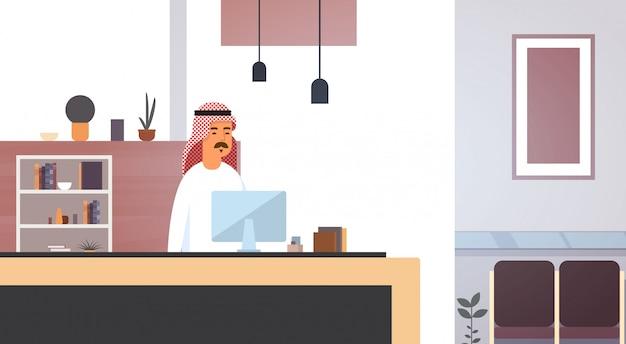 Homem de negócios árabes, usando o computador muçulmano empreendedor no escritório moderno Vetor Premium
