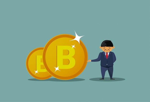 Homem de negócios asiáticos segurando moedas de bitcoins Vetor Premium