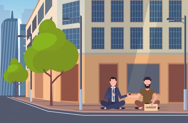 Homem de negócios, bebendo café, falando com o mendigo sentado na cidade rua placa com sinal implorando por ajuda sem-teto conceito desempregado edifício exterior cityscape cityscape comprimento total fundo horizontal Vetor Premium