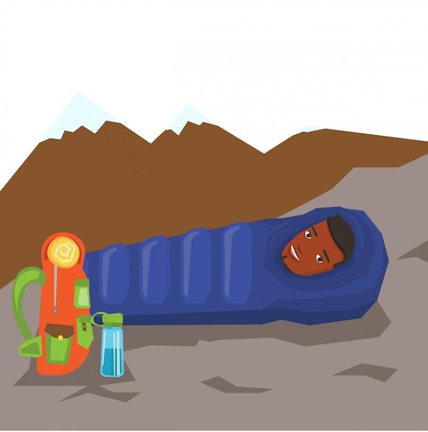 Homem descansando no saco de dormir nas montanhas. Vetor Premium