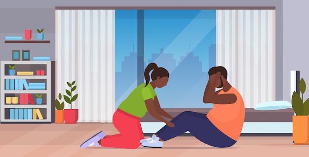 Homem gordo fazendo abdominais exercícios com excesso de peso mulher segurando suas pernas pares treino juntos conceito perda de peso conceito moderno sala interior comprimento total horizontal Vetor Premium