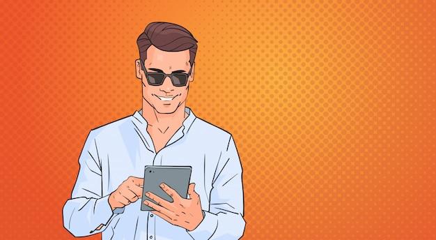Homem jovem, usando, tabuleta, redes computador, online, sobre, pop arte, coloridos, retro, estilo, fundo Vetor Premium
