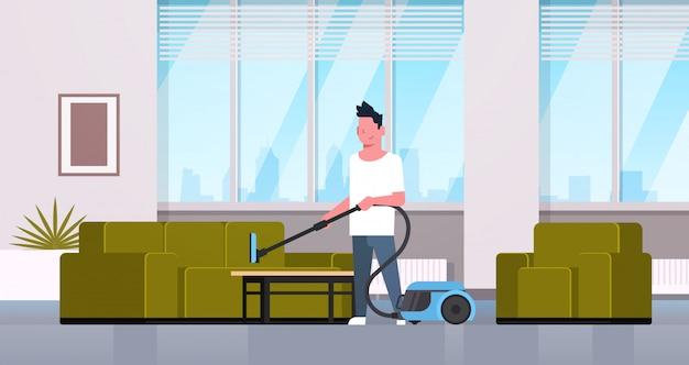 Homem limpeza sofá com aspirador cara fazendo trabalho doméstico conceito moderna sala interior masculino personagem de desenho animado Vetor Premium