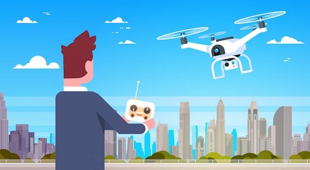 Homem negócio, segurando, controle remoto, para, modernos, zangão, mosca, sobre, cidade, edifícios Vetor Premium