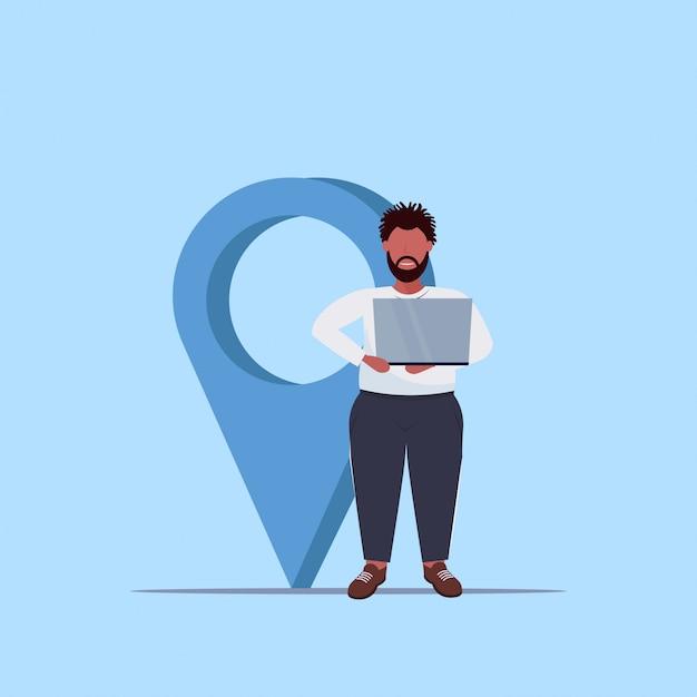 Homem, usando, geo tag, ponteiro, americano africano, sujeito, segurando, laptop, perto, local, marcador, gps, navegação, conceito, comprimento total Vetor Premium