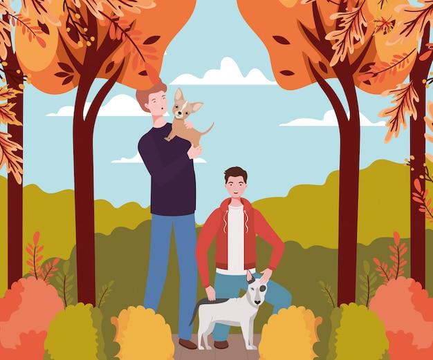 Homens jovens com mascotes de cães fofos no acampamento de outono Vetor Premium