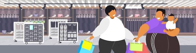 Homens obesos gordos com criança segurando sacos de compras com excesso de peso caras com criança andando juntos grande venda obesidade conceito moderno boutique moda retrato interior Vetor Premium