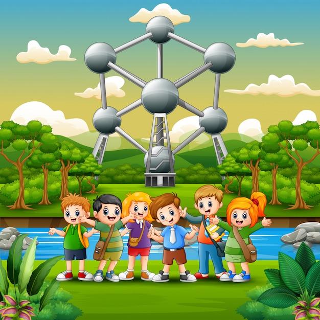 Ilustração de crianças em idade escolar feliz em pé na frente do atomium Vetor Premium
