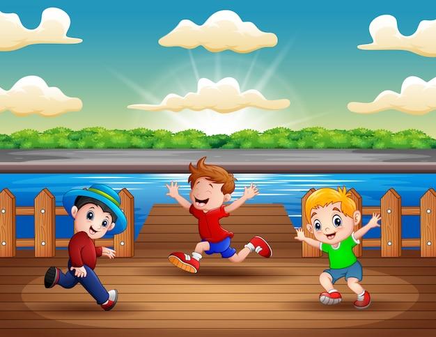 Ilustração, de, três meninos, executando, em, a, porto Vetor Premium
