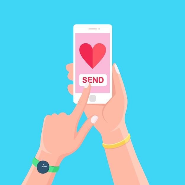 Ilustração do dia dos namorados. envie ou receba amor sms, carta, e-mail com o celular. celular branco com o ícone de um coração vermelho na mão no fundo. Vetor Premium
