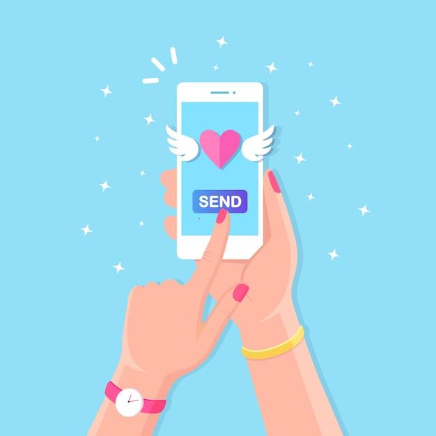 Ilustração do dia dos namorados. envie ou receba amor sms, carta, e-mail com o celular. celular branco na mão no fundo. voando coração vermelho com asas. Vetor Premium