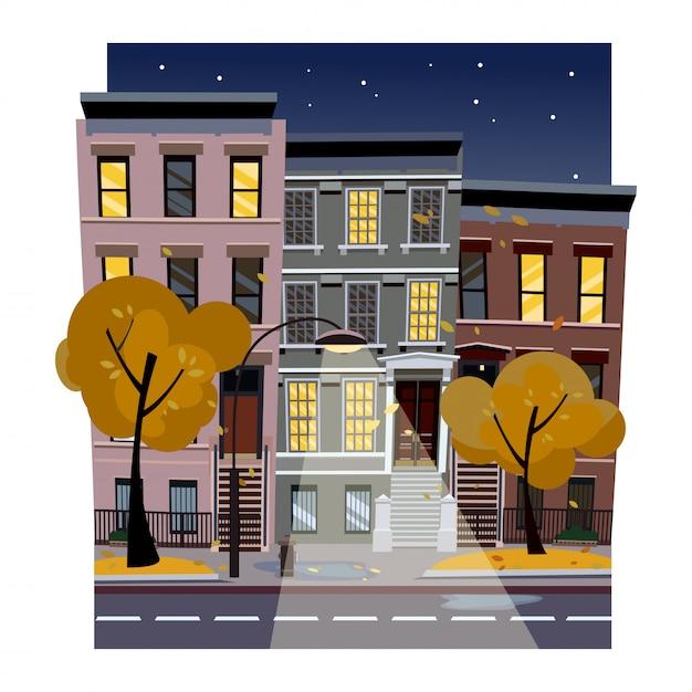 Ilustração lisa do vetor dos desenhos animados da rua chuvosa da cidade do outono na noite. casas irregulares com janelas luminosas Vetor Premium