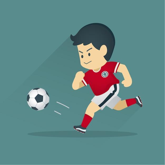Jogador de futebol chutando uma bola Vetor Premium