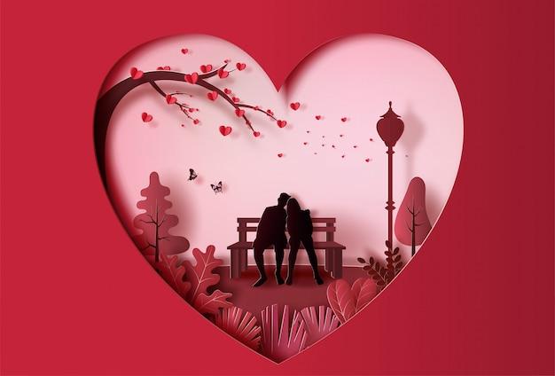 Jovem casal apaixonado, sentado em um banco no parque, estilo de arte de papel. Vetor Premium