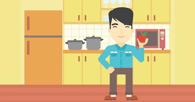 Jovem com maçã na cozinha. Vetor Premium