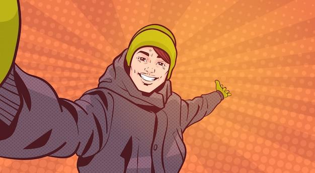 Jovem em roupas de inverno tirar foto selfie apontando a mão para copiar o espaço sobre fundo colorido estilo retro Vetor Premium