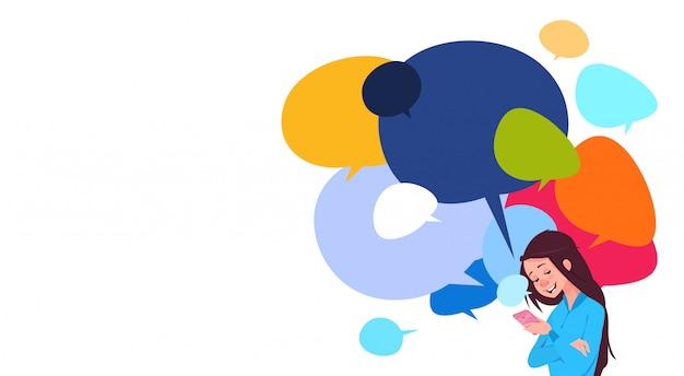 Jovem, menina, messaging, segurando, célula, esperto, telefones, sobre, coloridos, conversa, bolhas, fundo, social, mídia Vetor Premium