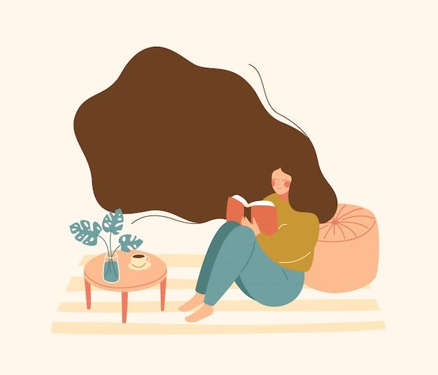 Jovem mulher com cabelo flutuante, senta-se no chão e lê o livro. Vetor Premium