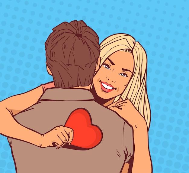 Linda garota abraçar homem segurando coração vermelho feliz sorrindo sobre quadrinhos pop art dia dos namorados férias conceito Vetor Premium