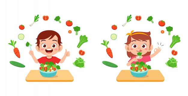 Lindos meninos felizes comem frutas vegetais de salada Vetor Premium