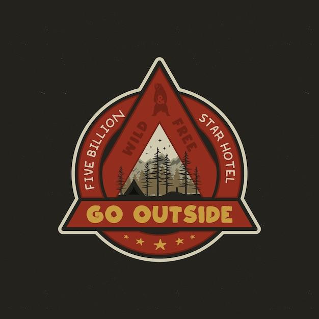 Logotipo da aventura desenhada de mão com barraca de acampamento, montanhas, floresta de pinheiros. Vetor Premium