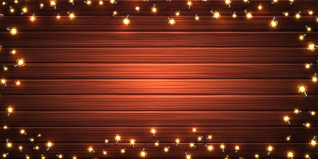 Luzes de natal. guirlandas de natal brilhante de lâmpadas led na textura de madeira. decorações de férias de lâmpadas coloridas realistas Vetor Premium