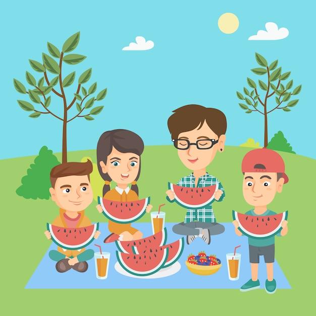 Mãe com filhos comendo melancia no parque. Vetor Premium