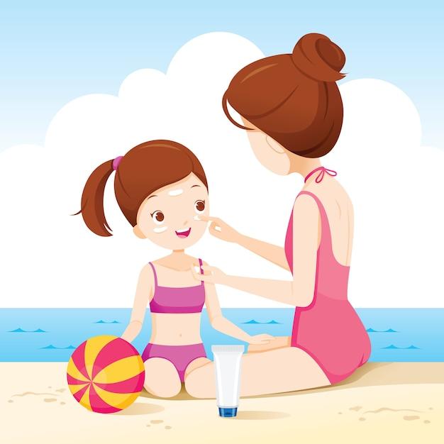 Mãe usando protetor solar no rosto da filha na praia Vetor Premium