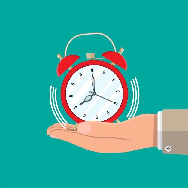 Mão com despertador vermelho. controle de estratégia e tarefas, projetos de negócios, planejamento de gerenciamento de tempo, prazo. gerenciamento de tempo. estilo simples de ilustração vetorial Vetor Premium