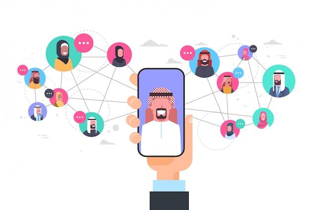 Mão de homem árabe segurando o conceito de comunicação de rede de telefone inteligente grupo de conexão de pessoas árabe Vetor Premium