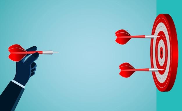 Mão de um homem de negócios, jogando um dardo vermelho no alvo Vetor Premium