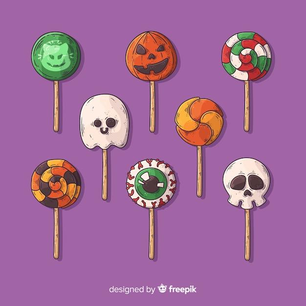 Mão desenhada coleção de doces de halloween em fundo violeta Vetor grátis