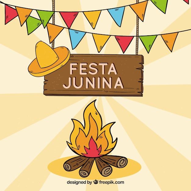 Mão desenhada festa junina fundo com fogueira Vetor grátis