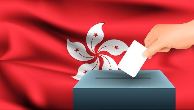 Mão masculina pousa uma folha de papel branca com uma marca como símbolo de um boletim de voto no fundo da bandeira de hong kong. Vetor Premium