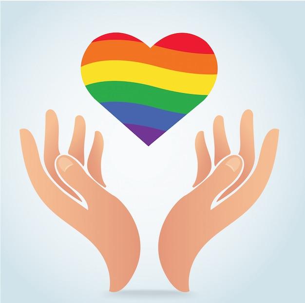 Mão segurando a bandeira de arco-íris no ícone de forma de coração Vetor Premium